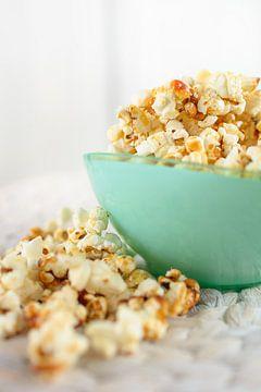 Frisch gemachtes Popcorn liegt in einer Schale auf einem Tisch. von Edith Albuschat