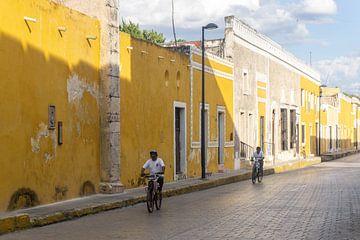 Fietsers in de gele stad Izamal in Mexico van Reis Genie
