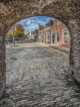 Doorkijkje vanuit de poort in de stadsmuur op een straat in Sloten, Friesland. sur Harrie Muis