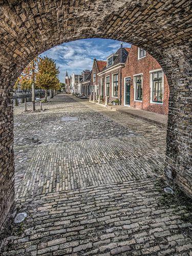 Doorkijkje vanuit de poort in de stadsmuur op een straat in Sloten, Friesland. van Harrie Muis