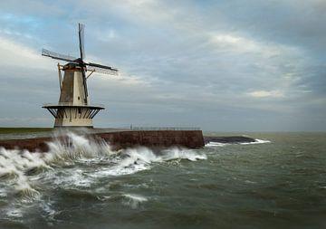 Stürmisches Wetter an der Nordsee mit Wellen, die den Deich mit der Windmühle an der Spitze zerschel von Jos Pannekoek