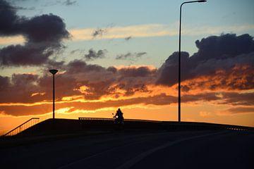 Scooterrijder tijdens zonsondergang van Jurjen Jan Snikkenburg