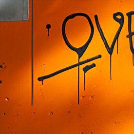 Liefdevolle grafitti op oranje muur van Maerten Prins