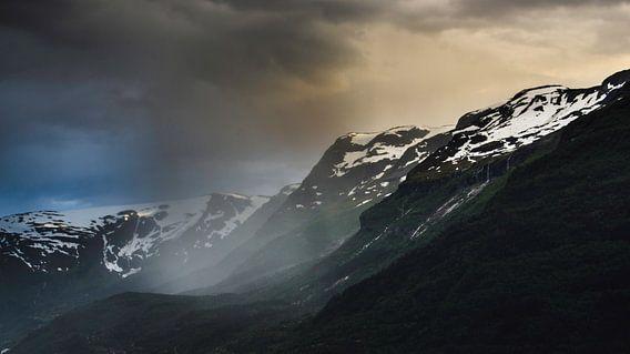 Een plaatselijke regenbui in de hardangerfjord in Noorwegen. De zonsondergang maakte het mogelijk om een deze wat duistere compositie te schieten. De ondergaande zon achter de bergen gaven de wolken rechts van de regenbui een wat aardse kleur terwijl meer in de verte en links van de regenbui de lucht mooie blauw is. Deze foto is gemaakt vanaf het plaatsje Lofthus aan één van de zijtakken van de Hardangerfjord.