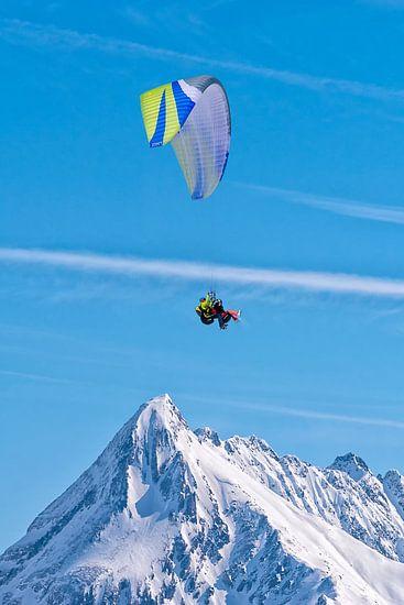 Paragliden boven de besneeuwde bergtop