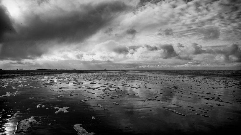 De heerlijke wolkenlucht reflecteert prachtig in het water van de zee van Studio de Waay