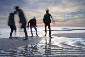 Silhouetten steken af tegen de zonsondergang op het strand van Julianadorp van Gerben van Dijk