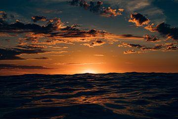 Die untergehende Sonne versteckt sich hinter einer hohen Welle am Nordseestrand von Terschelling von Alex Hamstra