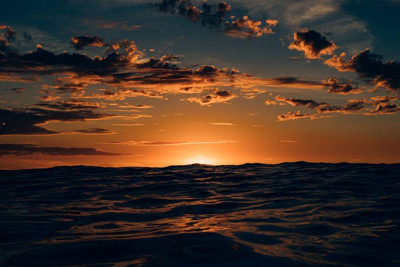 De ondergaande zon verschuilt zich achter een hoge golf bij het noordzeestrand van Terschelling van Alex Hamstra