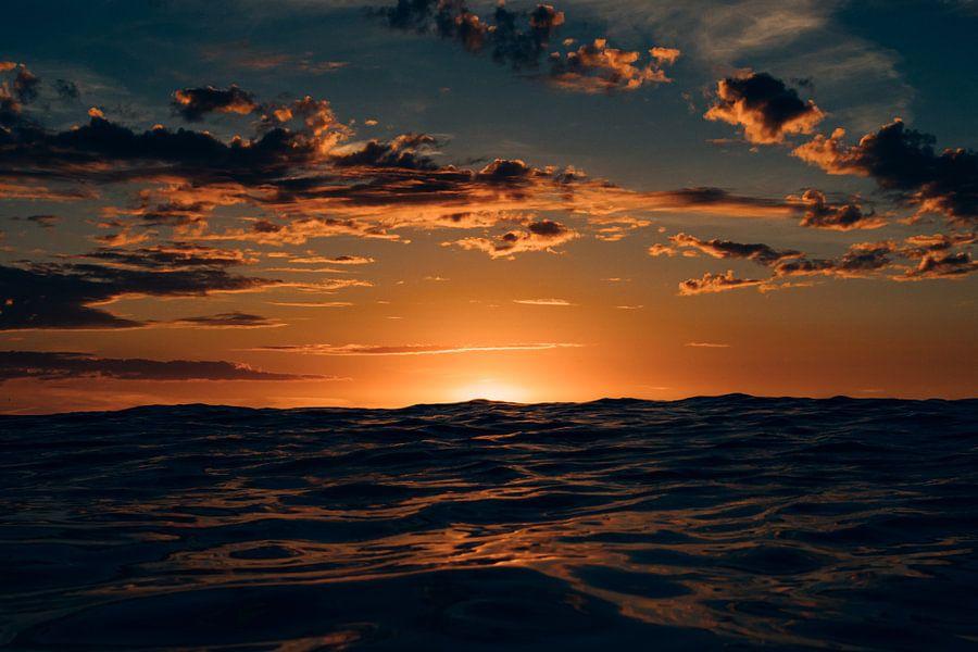 De ondergaande zon verschuilt zich achter een hoge golf bij het noordzeestrand van Terschelling