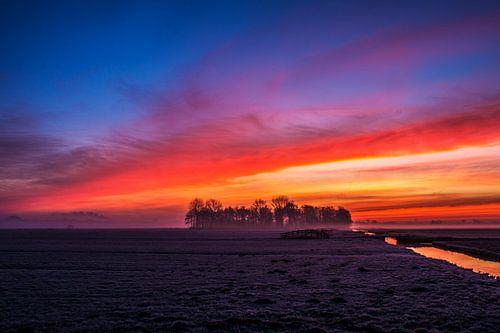 Vuurrode zonsopgang in de polder