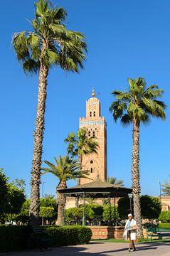 Gebakjesverkoper in park met palmbomen voor minaret Koutoubia moskee in Marrakech Marokko van Dieter Walther