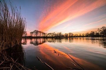 Abendrot über dem Wasser eines Sees von Menno van der Haven