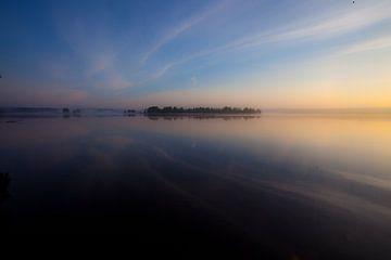 De dageraad op het meer. De blauwe en scharlakenrode hemel wordt gereflecteerd in het stille water v van Michael Semenov