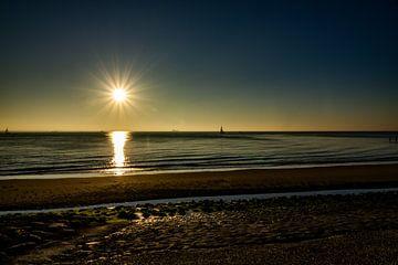 Zonsondergang aan de kust met een zeilboot van Kirsten van de Groep