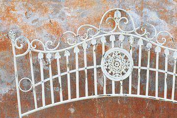 Romantisch vintage verweerd metalen hek tegen verweerde muur van Annavee