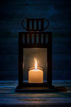 Windlicht met brandende kaars op houten tafel in close-up van Jenco van Zalk