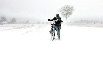 Meisje met fiets in sneeuwstorm in Zeeland van Wout Kok