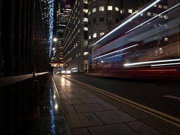 Typische hop-on-hop-off bus rijdend door Canary Wharf van Matthijs Noordeloos
