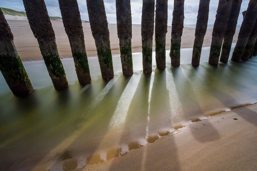 Zeewering palen met schaduw van Mark Scheper