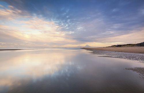 Reflecties op een nat strand bij zonsondergang van
