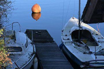 Twee vuile boten aan een dok en een oranje boei in het blauwe kalme water van een meer wachten op he van Maren Winter