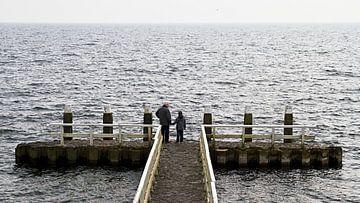 Opa en kleinzoon kijken naar het meer.  von Ron Van Rutten
