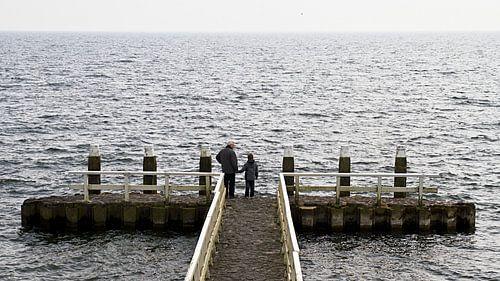 Opa en kleinzoon kijken naar het meer.  van Ron van Rutten
