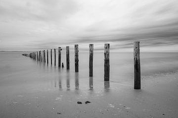 Strandpalen in zee op een bewolkte dag van Sjoerd van der Wal