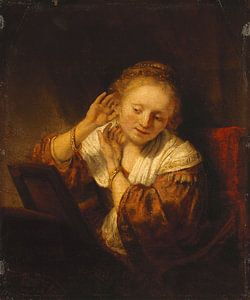 Junge Frau, die Ohrringe anprobiert - Rembrandt van Rijn