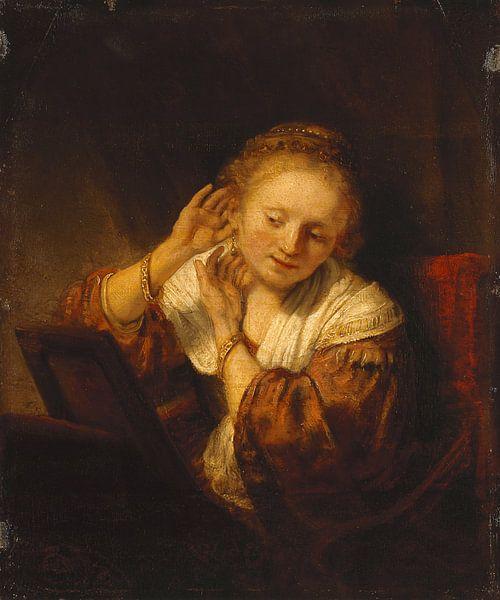 Junge Frau, die Ohrringe anprobiert - Rembrandt van Rijn von Rembrandt van Rijn