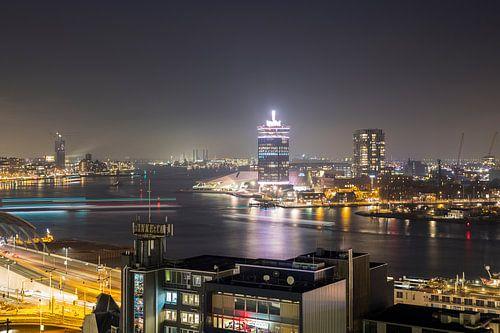 Pontjes in de avond trekken lijnen op het IJ in Amsterdam van