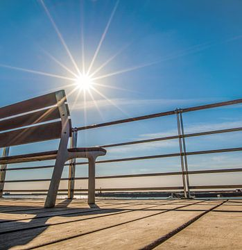 Zomersfeer, een leeg bankje in het tegenlicht van de zon sur Harrie Muis
