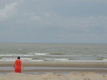 vrouw in rood aan zee van