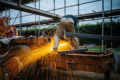 Corsobouwer aan het ijzer slijpen