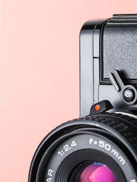 Macro close-up van detail van vintage  'Praktica' camera met roze/oranje pastel kleurige achtergrond van Iris Koopmans