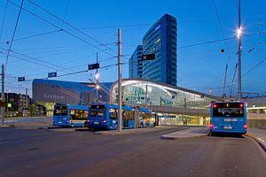 Trolleybussen in Arnhem voor het centraal station in de nacht.