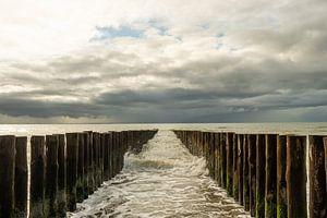 Zee met golfbrekers en aanstormend water. van Helene van Rijn