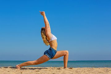 Junge Niederländerin in Sommerkleidung praktiziert Yoga am Strand von Hurghada in Ägypten von Ben Schonewille