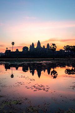 Zonsopkomst met felle kleuren en een weerspiegeling van de Angkor Wat tempel in Cambodja. van Twan Bankers