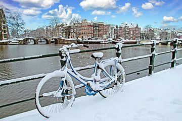 Besneeuwde fiets aan de Amstel in Amsterdam in winter van