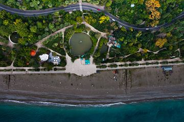 Vertikale Luftaufnahme eines Strandes, einer schönen Parkstraße. Foto von oben nach unten, blaues Wa von Michael Semenov