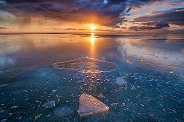 Winterlandschap met ijs op het IJsselmeer bij Workum tijdens zonsondergang met een warme winterzon van Bas Meelker
