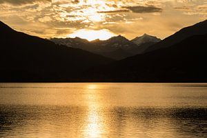 Meer en bergen bij zonsondergang