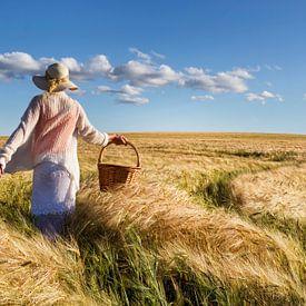 Vrouw met hoed en mand struint door graanveld van Beeldig Beeld