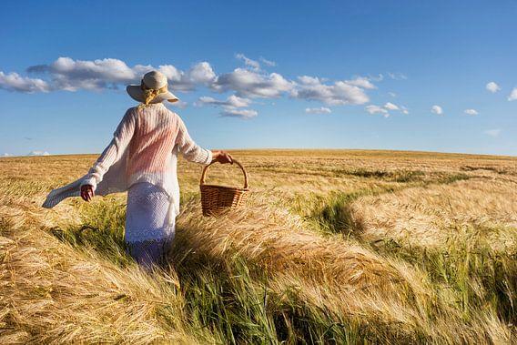 Vrouw met hoed en mand struint door graanveld