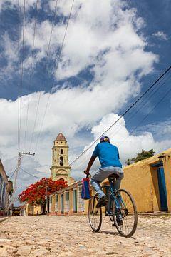 Mann und Fahrrad über eine holprige Straße in Trinidad, Kuba von Bart van Eijden