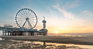 Pier Scheveningen reuzenrad bij zonsondergang vanaf het strand. Weerspiegeling in het water. Zon die van Erik van 't Hof
