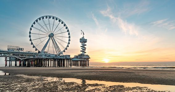 Pier Scheveningen reuzenrad bij zonsondergang vanaf het strand. Weerspiegeling in het water. Zon die