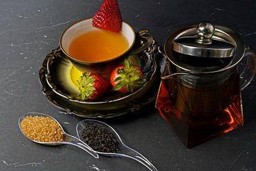Thé noir à la fraise dans une tasse et une théière en verre avec du théa sur Babetts Bildergalerie